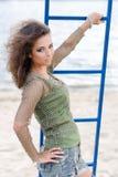 Όμορφη νέα γυναίκα στην τοποθέτηση κάλυψης στην παραλία Στρατιωτική μόδα στοκ φωτογραφία με δικαίωμα ελεύθερης χρήσης