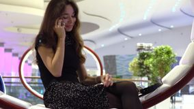 Όμορφη νέα γυναίκα στη μαύρη ομιλία στο τηλέφωνό της σε ένα σύγχρονο εσωτερικό 4K βίντεο απόθεμα βίντεο