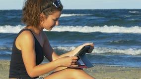 Όμορφη νέα γυναίκα στη ρομαντική διάθεση που κρατά ένα PC ταμπλετών θαλασσίως απόθεμα βίντεο