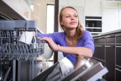 Όμορφη, νέα γυναίκα στη σύγχρονη και καλά εξοπλισμένη κουζίνα της Στοκ Εικόνες