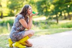 Όμορφη νέα γυναίκα στις κίτρινες μπότες βροχής με το λαστιχένιο βάτραχο παιχνιδιών Στοκ εικόνες με δικαίωμα ελεύθερης χρήσης