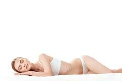 Όμορφη νέα γυναίκα στον άσπρο ύπνο εσώρουχων που απομονώνεται στο λευκό Στοκ φωτογραφίες με δικαίωμα ελεύθερης χρήσης