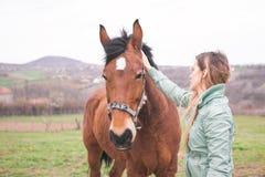 Όμορφη νέα γυναίκα στο αγρόκτημα με ένα καφετί άλογο Στοκ φωτογραφία με δικαίωμα ελεύθερης χρήσης