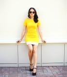 Όμορφη νέα γυναίκα στο κίτρινο φόρεμα και τα μαύρα γυαλιά ηλίου Στοκ Εικόνες