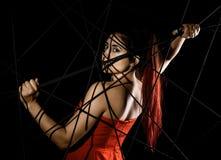 Όμορφη νέα γυναίκα στο κόκκινο φόρεμα που μπλέκεται σε έναν ιστό αράχνης σχοινιών σε ένα μαύρο υπόβαθρο στοκ φωτογραφίες