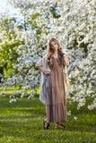 Όμορφη νέα γυναίκα στο μακροχρόνιο ύφος boho φορεμάτων στα πράσινα Η.Ε χλόης Στοκ Εικόνα