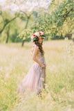 Όμορφη νέα γυναίκα στο μακρύ ιώδες φόρεμα με το στεφάνι στο κεφάλι που στέκεται πίσω υπαίθρια Στοκ Εικόνα