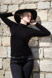 Όμορφη νέα γυναίκα στο Μαύρο με την τοποθέτηση μαύρων καπέλων κοντά στο ST Στοκ Εικόνα