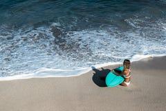Όμορφη νέα γυναίκα στο μπικίνι με τον πίνακα κυματωγών στην παραλία του τροπικού νησιού Στοκ Εικόνα
