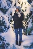 Όμορφη νέα γυναίκα στο πάρκο τη χιονίζοντας χειμερινή ημέρα Στοκ φωτογραφίες με δικαίωμα ελεύθερης χρήσης