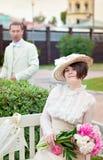Όμορφη νέα γυναίκα στο πορτρέτο φορεμάτων και καπέλων στο αναδρομικό ύφος Η κυρία κυρίων Ιματισμός μόδας στον τρύγο Στοκ Φωτογραφίες