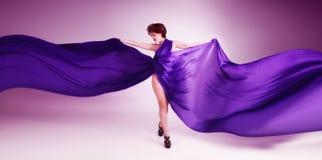 Όμορφη νέα γυναίκα στο πορφυρό φόρεμα στοκ εικόνα
