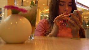 Όμορφη νέα γυναίκα στο ροζ που χρησιμοποιεί το τηλέφωνό της σε έναν καφέ Κινητός τηλεφωνικός εθισμός 4K βίντεο φιλμ μικρού μήκους