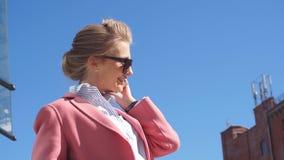 Όμορφη νέα γυναίκα στο ρόδινο παλτό που καλεί τηλεφωνικώς απόθεμα βίντεο