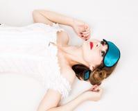 Όμορφη νέα γυναίκα στο ρόδινο φόρεμα και σημεία για τον ύπνο, στάση, τοποθέτηση μάτι ύπνου που καλύπτει τη μάσκα Στοκ φωτογραφία με δικαίωμα ελεύθερης χρήσης