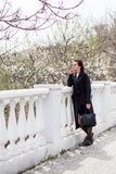 Όμορφη νέα γυναίκα στο σκοτεινό μάλλινο παλτό στο χρόνο οδών την άνοιξη Το αμύγδαλο ανθίζει τα άνθη, που φορούν το καθιερώνον τη  στοκ εικόνα με δικαίωμα ελεύθερης χρήσης