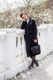 Όμορφη νέα γυναίκα στο σκοτεινό μάλλινο παλτό στο χρόνο οδών την άνοιξη Το αμύγδαλο ανθίζει τα άνθη, που φορούν το καθιερώνον τη  στοκ φωτογραφία με δικαίωμα ελεύθερης χρήσης