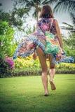 Όμορφη νέα γυναίκα στο pareo και μαγιό που περπατά στο πάρκο becah με την τσάντα την ηλιόλουστη θερινή ημέρα Τροπικό νησί Μπαλί Στοκ Φωτογραφίες