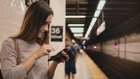 Όμορφη νέα γυναίκα στο smartphone και το πορτοφόλι εκμετάλλευσης πλατφορμώ απόθεμα βίντεο