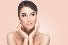 Όμορφη νέα γυναίκα σχετικά με το πρόσωπό της, Skincare, τέλειο δέρμα, Στοκ Εικόνες