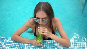 Όμορφη νέα γυναίκα το καλοκαίρι Χαλάρωση κοριτσιών μπικινιών στην τροπική πισίνα γυναίκα που πίνει ένα κοκτέιλ mojito απόθεμα βίντεο