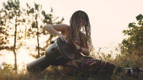 Όμορφη νέα γυναίκα χίπηδων με τα dreadlocks που παίζουν στο djembe Φοβιτσιάρης γυναίκα που παίζει τύμπανο στη φύση σε ένα εθνικό  φιλμ μικρού μήκους