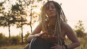 Όμορφη νέα γυναίκα χίπηδων με τα dreadlocks που παίζουν στο djembe Φοβιτσιάρης γυναίκα που παίζει τύμπανο στη φύση σε ένα εθνικό  απόθεμα βίντεο