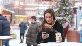 Όμορφη νέα γυναίκα χρησιμοποιώντας ένα smartphone και πίνοντας το καυτό τσάι κατά τη διάρκεια της έκθεσης Χριστουγέννων απόθεμα βίντεο