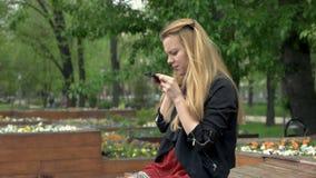 Όμορφη νέα γυναίκα χρησιμοποιώντας ένα smartphone στο θερινό πάρκο και κάνοντας selfie απόθεμα βίντεο