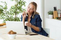 Όμορφη νέα γυναίκα χρησιμοποιώντας το lap-top της και τρώγοντας το γιαούρτι στο σπίτι Στοκ Εικόνες