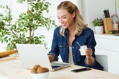 Όμορφη νέα γυναίκα χρησιμοποιώντας το lap-top της και τρώγοντας το γιαούρτι στο σπίτι Στοκ Φωτογραφία