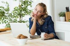 Όμορφη νέα γυναίκα χρησιμοποιώντας το lap-top της και τρώγοντας το γιαούρτι στο σπίτι Στοκ φωτογραφίες με δικαίωμα ελεύθερης χρήσης