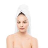 Όμορφη νέα γυναίκα brunette με το καθαρό πρόσωπο και πετσέτα στο κεφάλι της απομονωμένος Στοκ Εικόνες