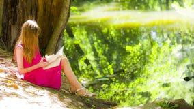 Όμορφη νέα γυναίκα brunette που διαβάζει ένα βιβλίο φιλμ μικρού μήκους