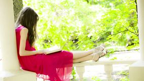 Όμορφη νέα γυναίκα brunette που διαβάζει ένα βιβλίο απόθεμα βίντεο