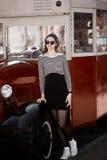 Όμορφη νέα γυναίκα brunette που φορά το φόρεμα, τα μαύρα γυαλιά κύκλων και το περπάτημα στην οδό, που θέτει κοντά στο αναδρομικό  Στοκ Φωτογραφίες
