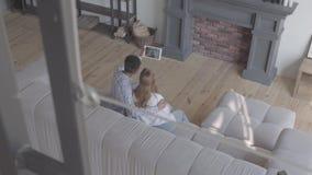 Όμορφη νέα διεθνής οικογένεια στο σπίτι, άνδρας αφροαμερικάνων και καυκάσια συνεδρίαση γυναικών στον καναπέ σε μεγάλο απόθεμα βίντεο