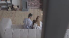 Όμορφη νέα διεθνής οικογένεια στο σπίτι, άνδρας αφροαμερικάνων, καυκάσια γυναίκα και μικρή συνεδρίαση κοριτσιών στον καναπέ απόθεμα βίντεο