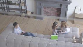 Όμορφη νέα διεθνής οικογένεια στο σπίτι, άνδρας αφροαμερικάνων, καυκάσια γυναίκα και κορίτσι στο μεγάλο καθιστικό φιλμ μικρού μήκους