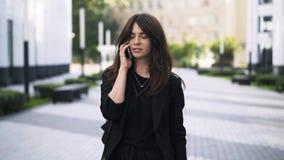 Όμορφη νέα επιχειρηματίας που έχει ένα τηλεφώνημα και ένα περπάτημα απόθεμα βίντεο