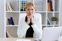 Όμορφη νέα επιχειρηματίας που εξετάζει τη κάμερα στο γραφείο Στοκ Φωτογραφία