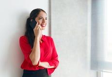 Όμορφη νέα επιχειρηματίας που μιλά πέρα από το τηλέφωνο σε έναν καναπέ Στοκ Φωτογραφία