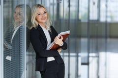Όμορφη νέα επιχειρηματίας που χαμογελά και που στέκεται με το φάκελλο στο γραφείο εξέταση τη κάμερα διάστημα αντιγράφων στοκ εικόνα