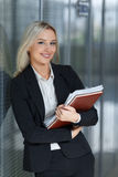 Όμορφη νέα επιχειρηματίας που χαμογελά και που στέκεται με το φάκελλο στο γραφείο εξέταση τη κάμερα στοκ φωτογραφία με δικαίωμα ελεύθερης χρήσης