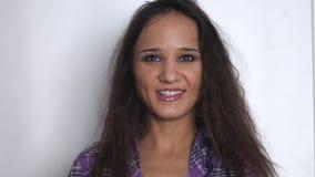 Όμορφη νέα επιχειρηματίας brunette που κοιτάζει και που χαμογελά πέρα από το άσπρο υπόβαθρο κίνηση αργή 3840x2160 φιλμ μικρού μήκους