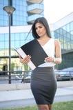 Όμορφη νέα επιχειρησιακή γυναίκα που εξετάζει τα έγγραφα εργασίας Στοκ φωτογραφία με δικαίωμα ελεύθερης χρήσης