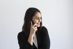 Όμορφη νέα επιχειρησιακή γυναίκα που μιλά στο κινητά τηλέφωνο και το s της στοκ φωτογραφία