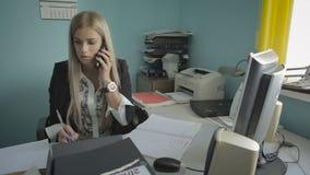 Όμορφη νέα επιχειρησιακή γυναίκα που μιλά στο τηλέφωνο στο βίντεο μήκους σε πόδηα αποθεμάτων γραφείων απόθεμα βίντεο
