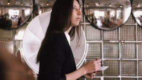 Όμορφη νέα επιχειρησιακή γυναίκα που τρώει ένα κέικ με ένα κουτάλι σε έναν καφέ σε ένα αντίθετο υπόβαθρο φραγμών φιλμ μικρού μήκους