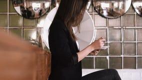 Όμορφη νέα επιχειρησιακή γυναίκα που τρώει ένα κέικ με ένα κουτάλι σε έναν καφέ σε ένα αντίθετο υπόβαθρο φραγμών απόθεμα βίντεο